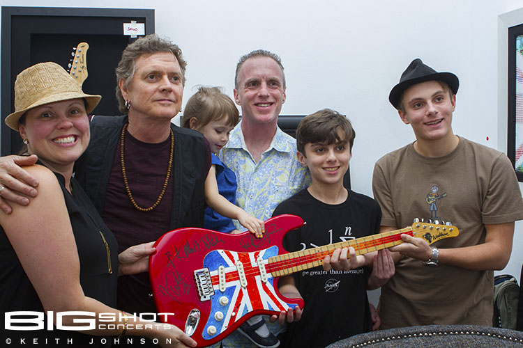 A young fan purchases a painted guitar from Rick Allen