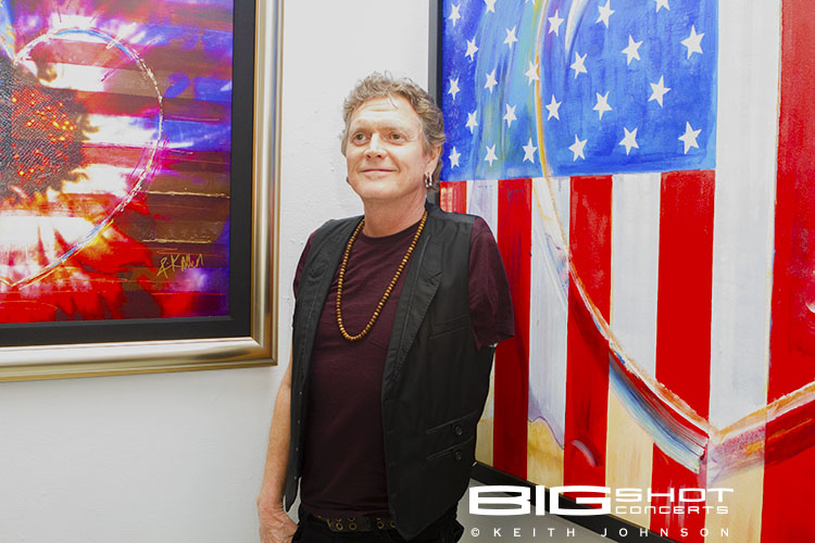 Drummer from England stands in front of American flag painting