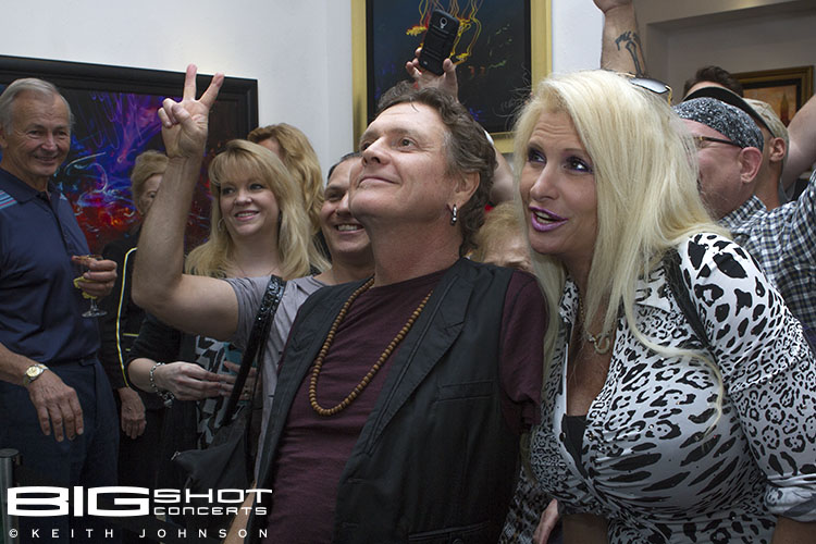 Rick Allen poses with a fan in front of his artwork